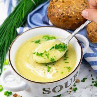 Blumenkohlsuppe in einer Suppenschüssel mit einer Hand, die einen Löffel mit Suppe hält sowie ein Brötchen und ein Bund Schnittlauch im Hintergrund