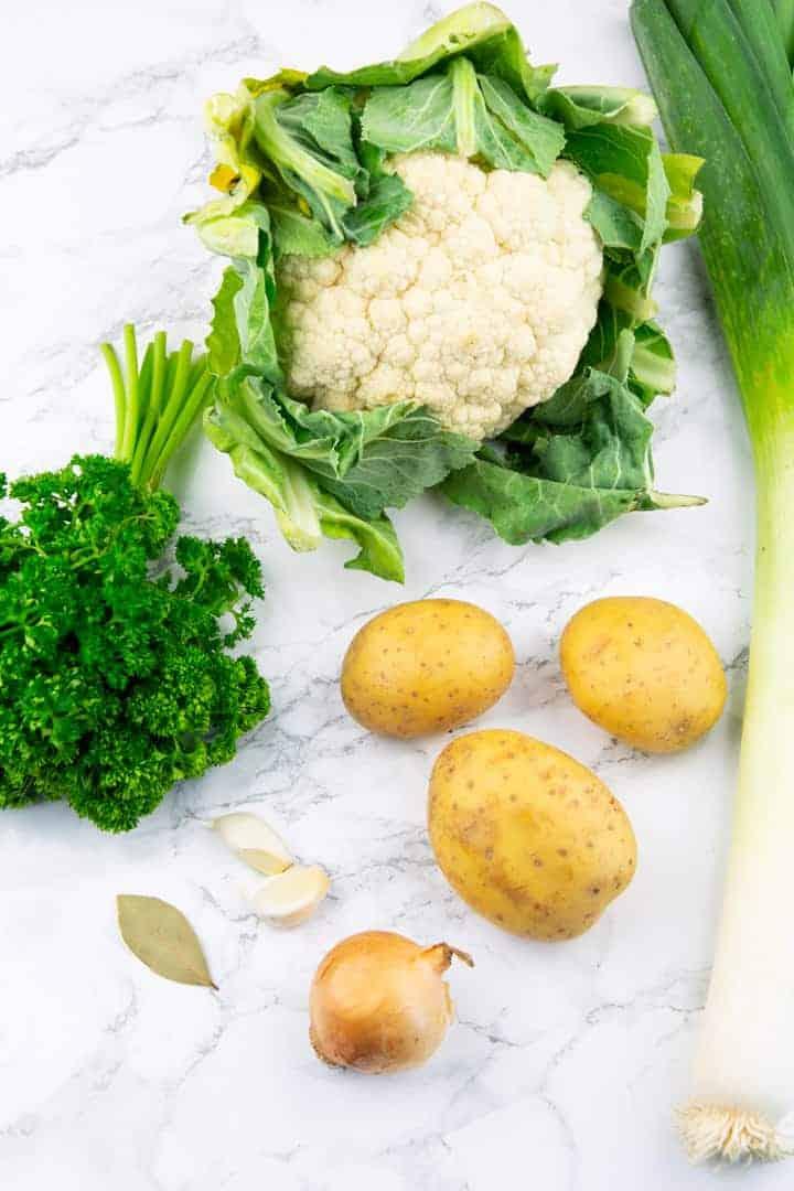 ein Blumenkphl, drei Kartoffel, eine Stange Lauch, eine Zwiebel und ein Bund Petersilie auf einer Marmorplatte