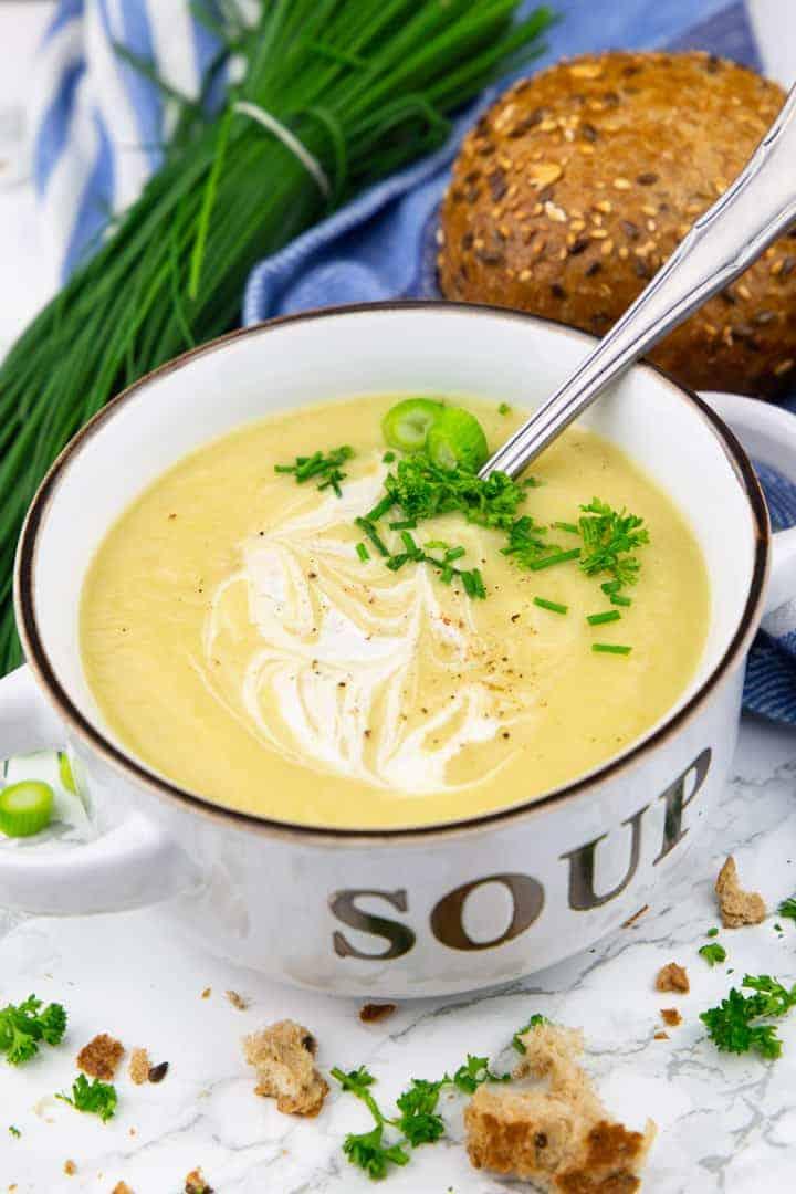 Blumenkohlsuppe in einer Suppentasse mit einem Löffel auf einer Marmorplatte mit einem Brötchen und einem Bund Schnittlauch im Hintergrund
