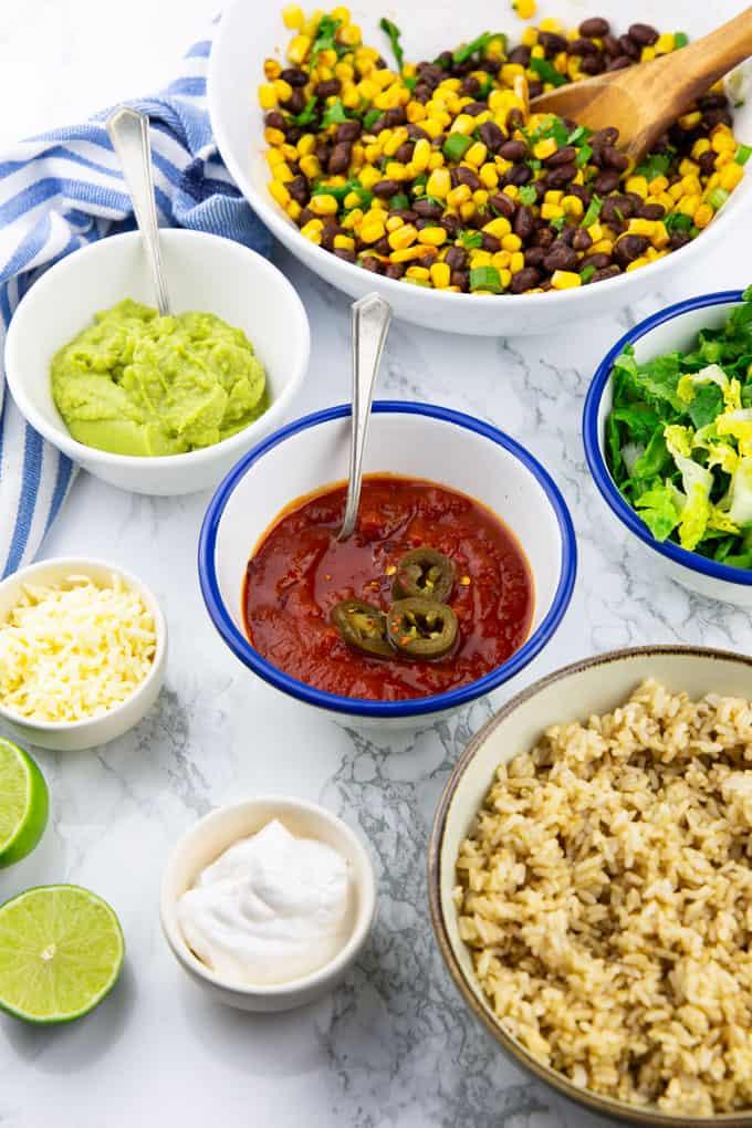 Zutaten für einen Burrito in Schälchen auf einer Marmorplatte (Reis, Salsa, Guacamole, Mais, Bohnen, Salat und Sour Cream)