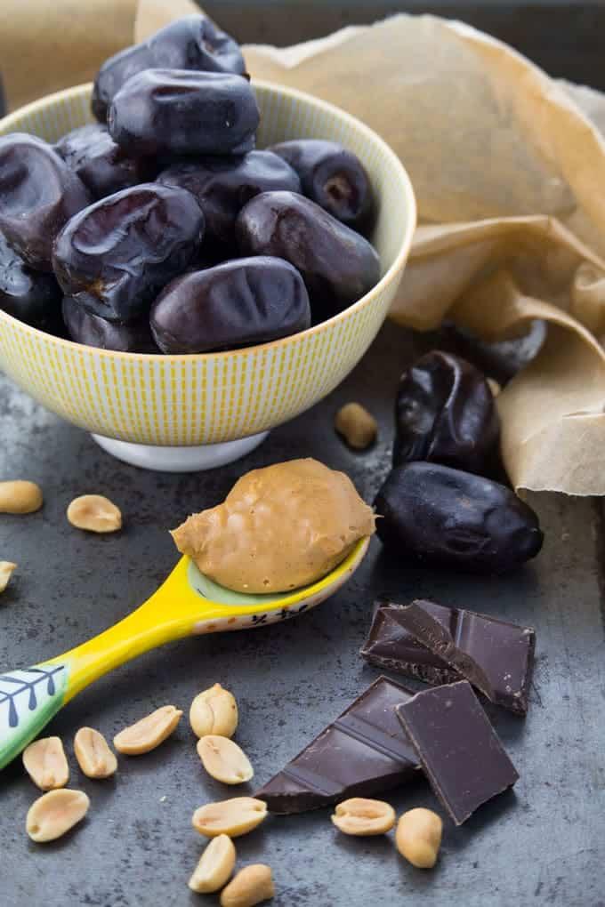 eine Schüssel mit Medjool Dates, ein Löffel mit Erdnussbutter, Zartbitterschokolade und Erdnusshälften auf einem Backblech