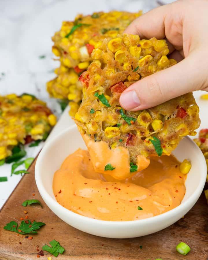 eine Hand, die einen Maispuffer in eine kleine Schüssel mit Paprika Mayonnaise tunkt