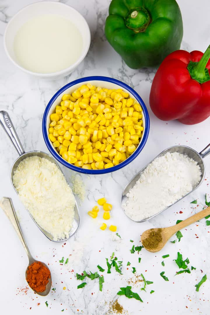eine kleine Schüssel Mais, eine grüne und eine rote Paprika, sowie zwei Messlöffel mit Mehl auf einer Marmorplatte