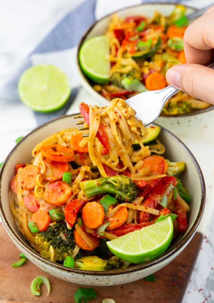 Asia Nudeln in zwei Tellern auf einem Holzschneidebrett mit einer Hand, die mit einer Gabel Nudeln aufrollt