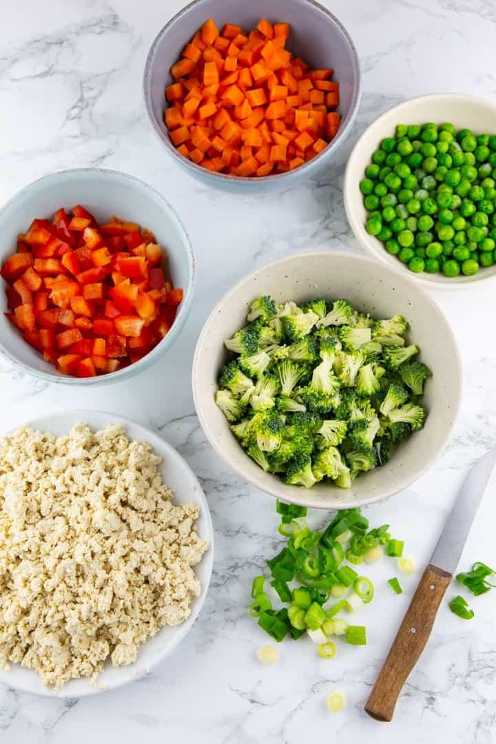 fünf Schälchen mit Reis sowie fein gewürfelter Paprika, Karotte, Brokkoli und Erbsen