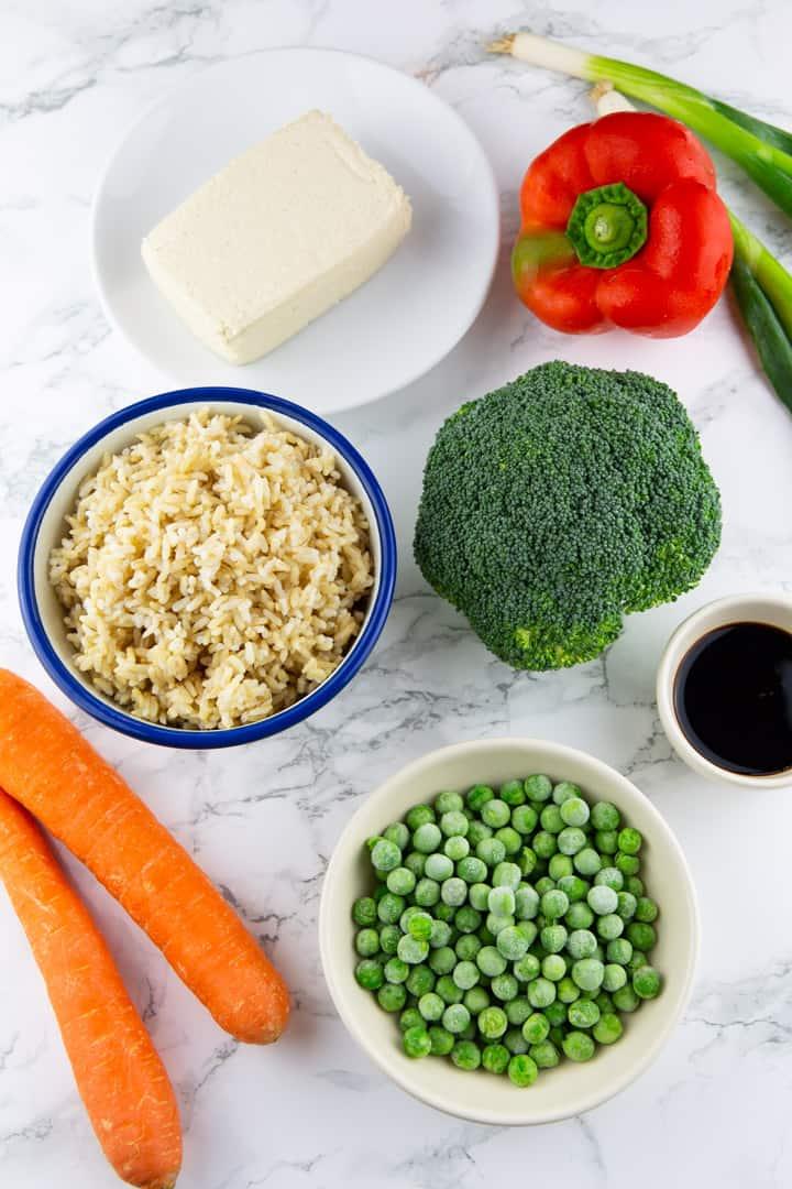 zwei Karotten, eine Paprika, ein Brokkoli, ein Schälchen mit Reis und ein Teller mit Tofu auf einer Marmorplatte