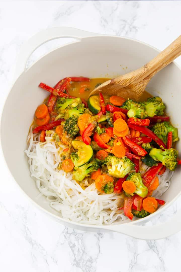 Reisnudeln in einer grauen Schüssel mit Paprika, Karotten und Brokkoli mit einem Kochlöffel auf einer Marmorplatte