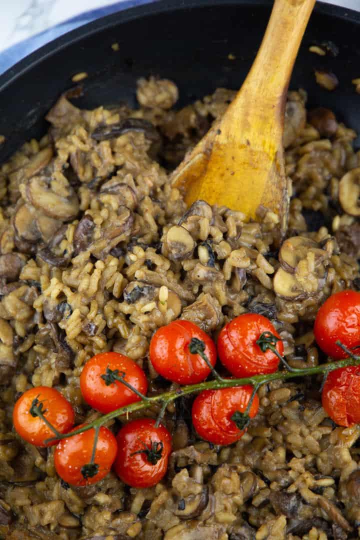 Nahaufnahme von einem Pilz Risotto mit Cherry Tomaten in einer schwarzen Pfanne mit einem Holzlöffel