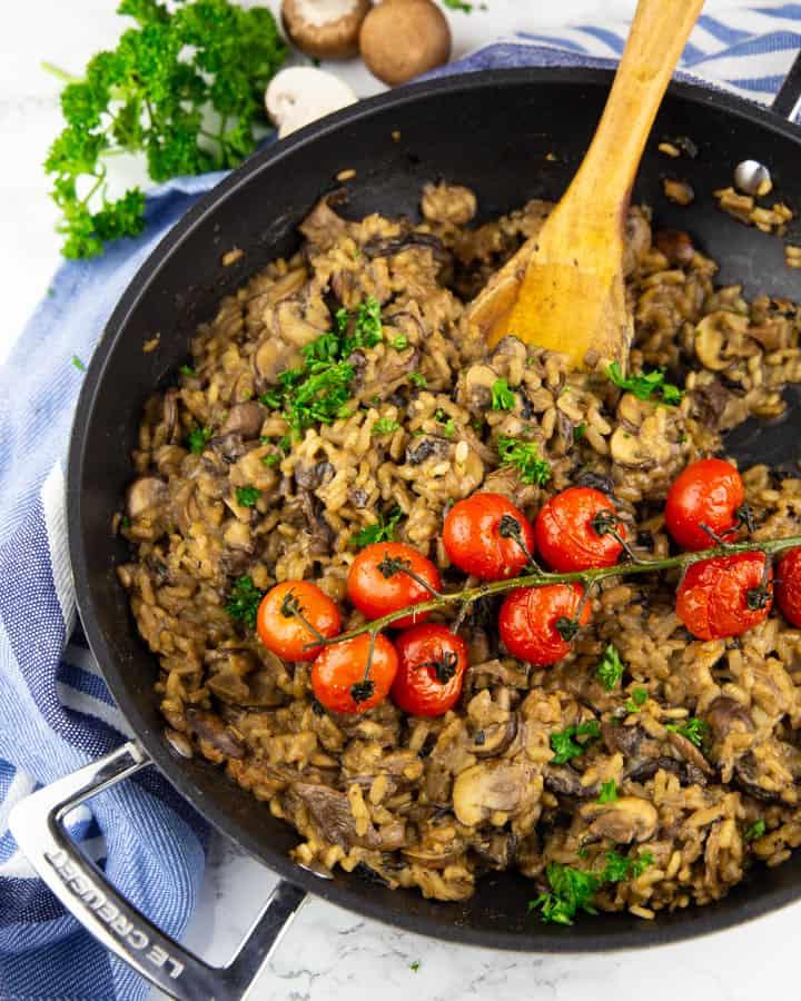 Risotto mit Pilzen in einer schwarzen Pfanne mit einem Holzlöffel auf einer Marmorplatte