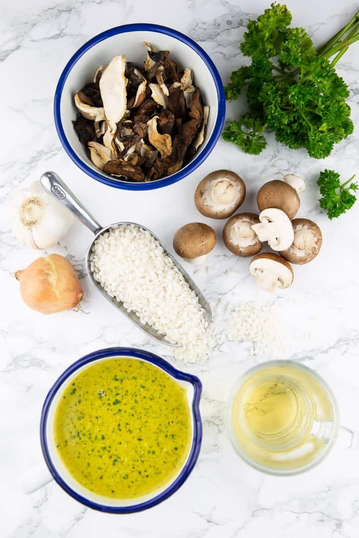 frische Champignons, getrocknete Pilze, Risottoreis, Petersilie, Gemüsebrühe, eine Zwiebel und Knoblauch auf einer Marmorplatte