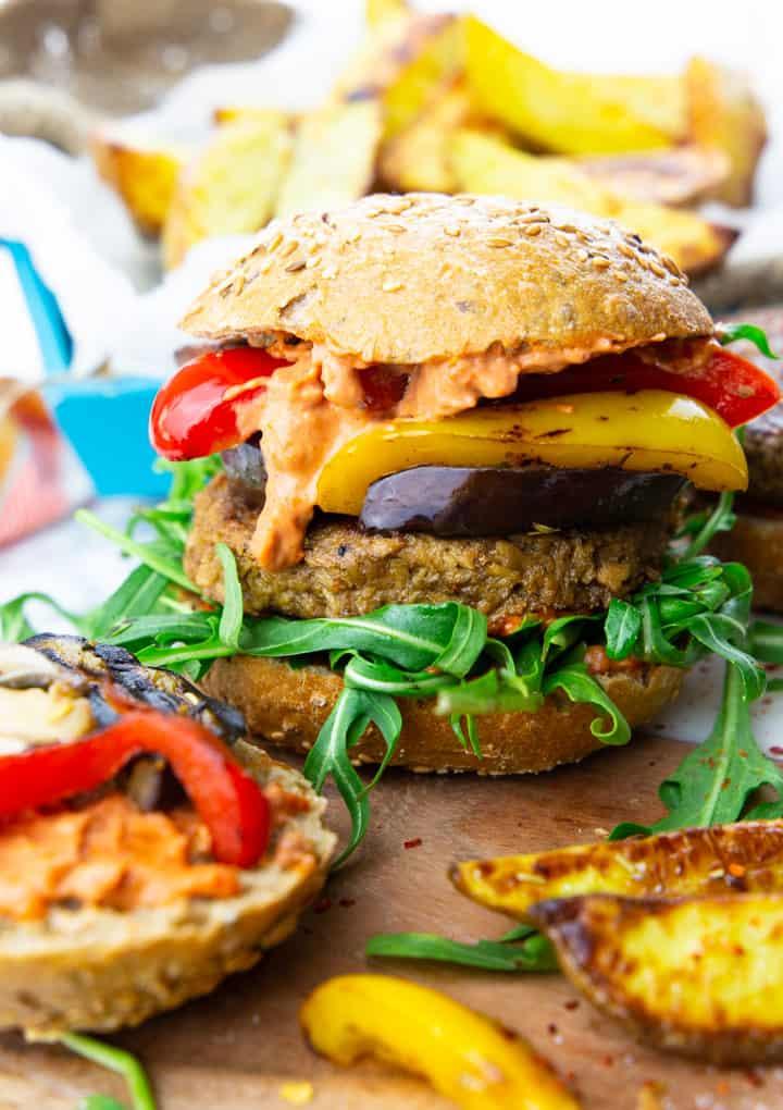 ein veganer Burger mit Grillgemüse und Rucola auf einem Holzbrett mit Kartoffelspalten im Hintergrund