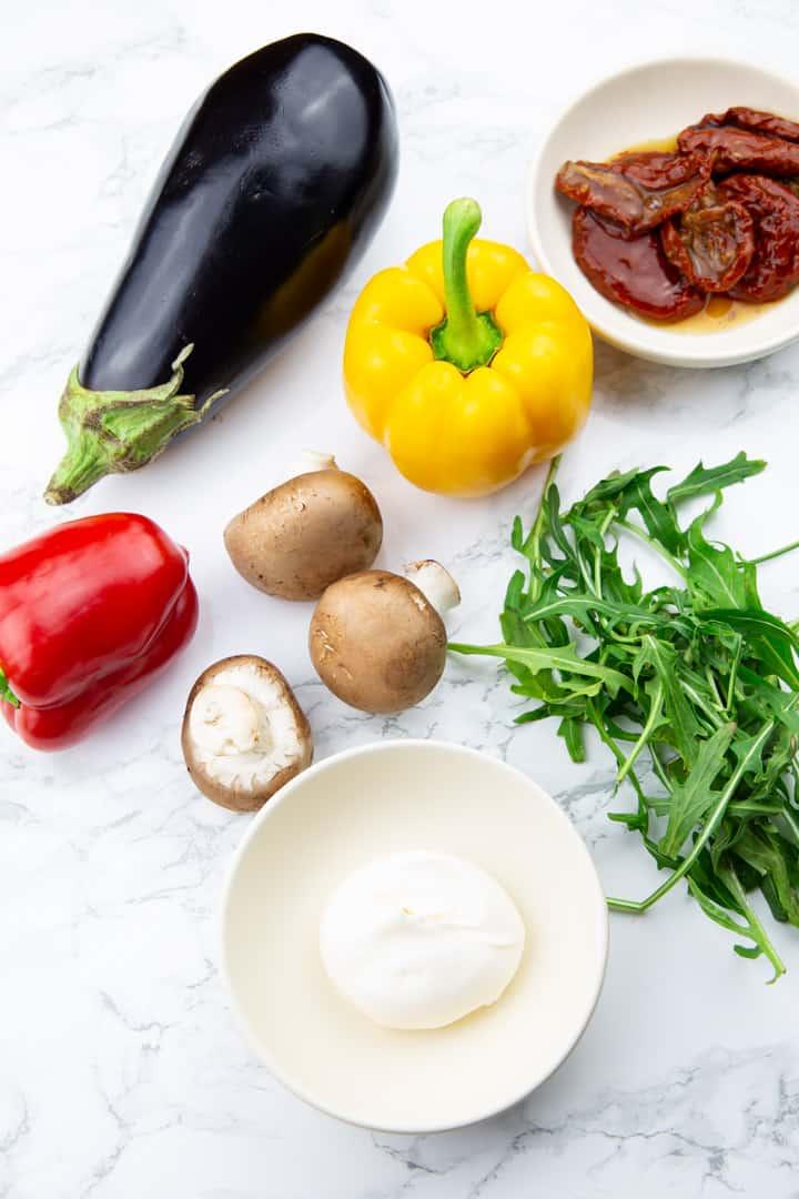 zwei Paprika, eine Aubergine, drei Champignons, Rucola, getrocknete Tomaten und Mayonnaise auf einer Marmorplatte