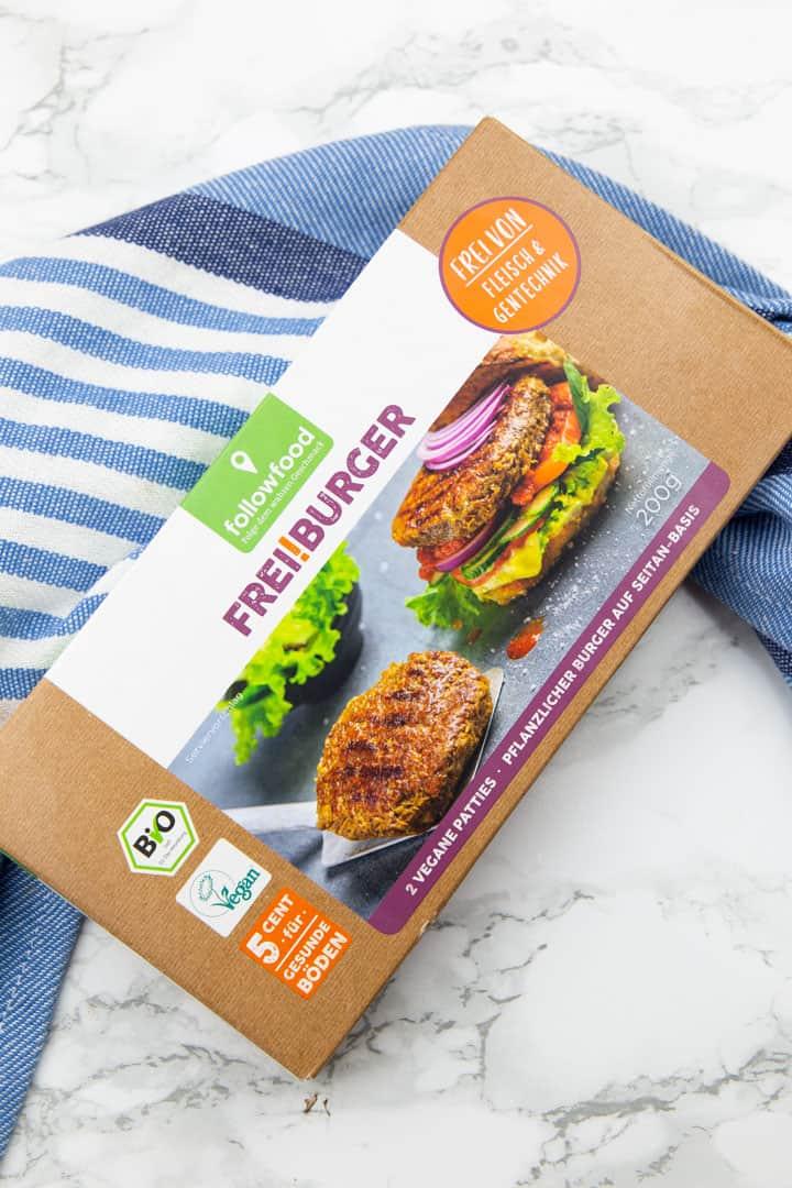 eine Packung mit veganen Burgern von followfood auf einer Marmorplatte