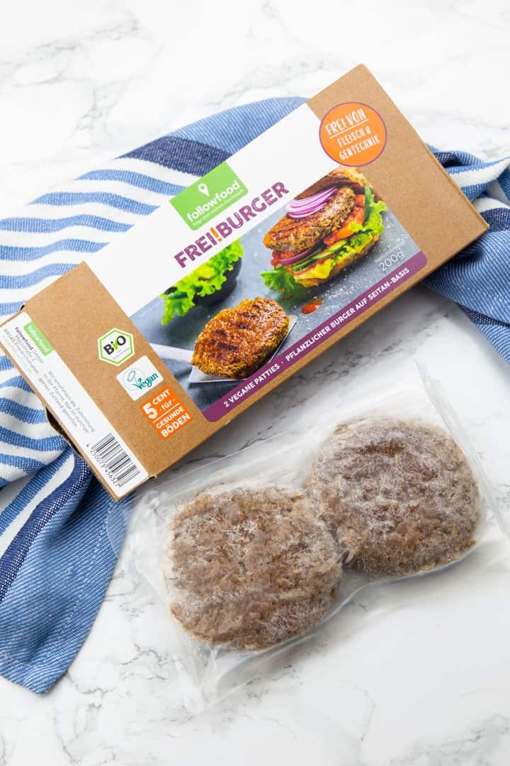eine Packung mit veganen Burgern von followfood auf einer Marmorplatte mit zwei eingeschweißten gefrorenen Burgern