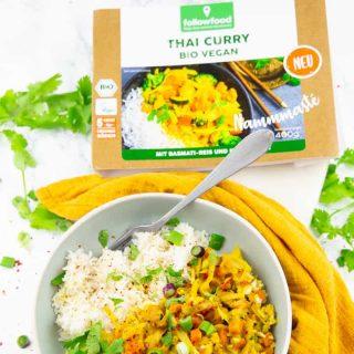 ein Teller mit Reis und veganem Thai Curry und einer Packung von followfood im Hintergrund