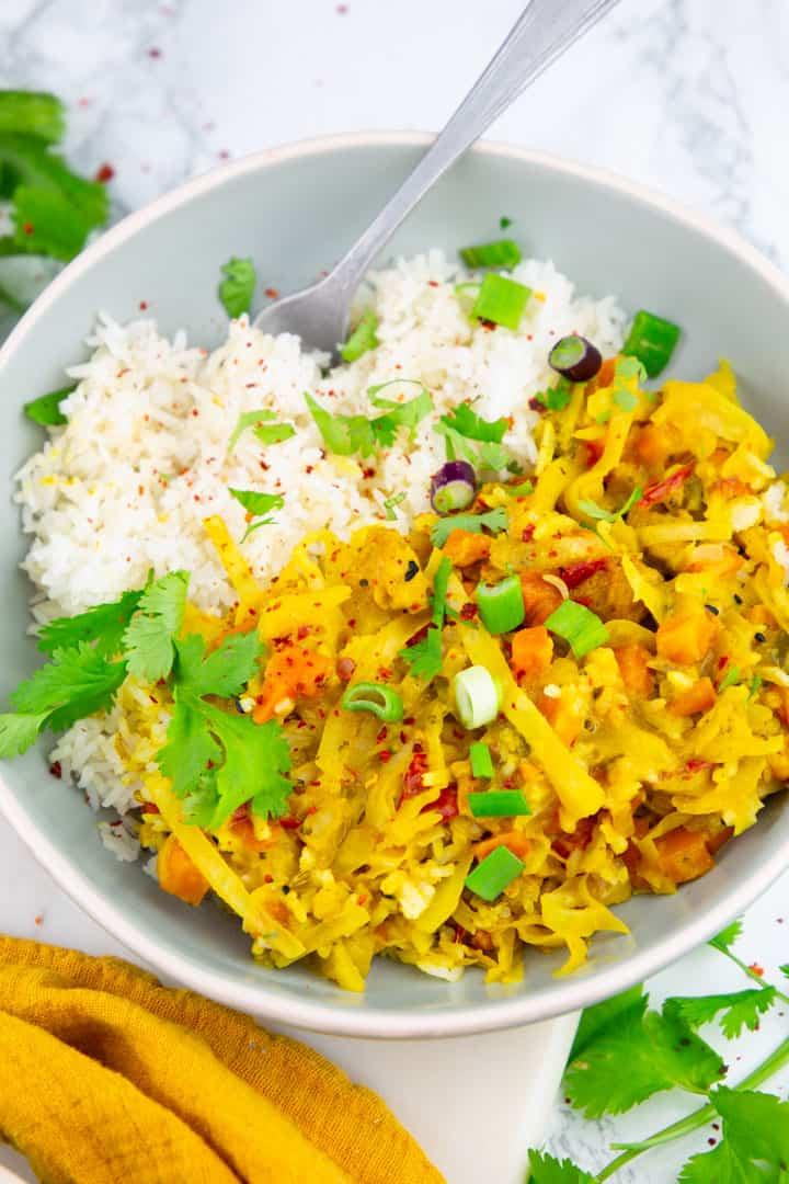 Thai Curry mit Basmati Reis in einem grauen Teller mit einem Löffel auf einer Marmorplatte