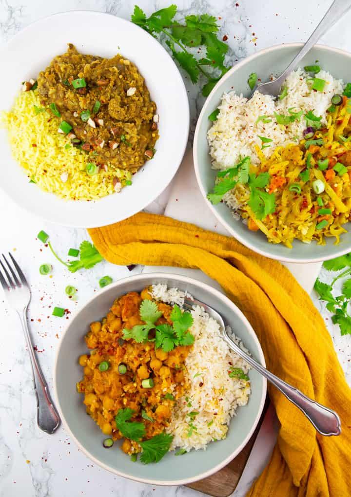 drei Teller mit Thai Curry, Linsen Dal und Kichererbsen Curry auf einer Marmorplatte mit frischem Koriander daneben