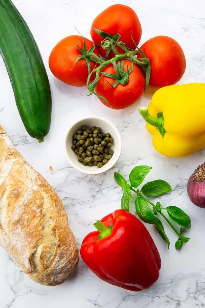 ein Ciabatta Brot, eine Gurke, vier Tomaten, zwei Paprika, eine kleine Schüssel Kapern und frischer Basilikum auf einer Marmorplatte