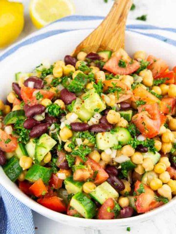 eine weiße Schüssel mit Kichererbsen Salat auf einer Marmorplatte mit Zitronen im Hintergrund