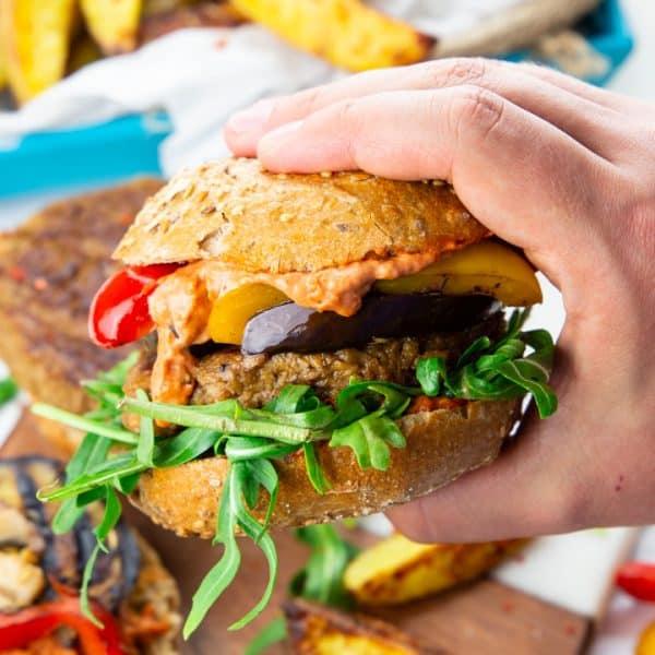 eine Hand, die einen veganen Burger mit Rucola in der Hand hält