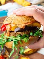 eine Hand, die einen veganen Burger hält mit Pommes und Grillgemüse im Hintergrund