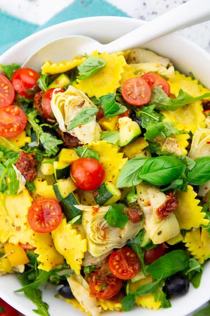 Nahaufnahme eines Ravioli Salats in einer weißen Schüssel mit einem weißen Löffel