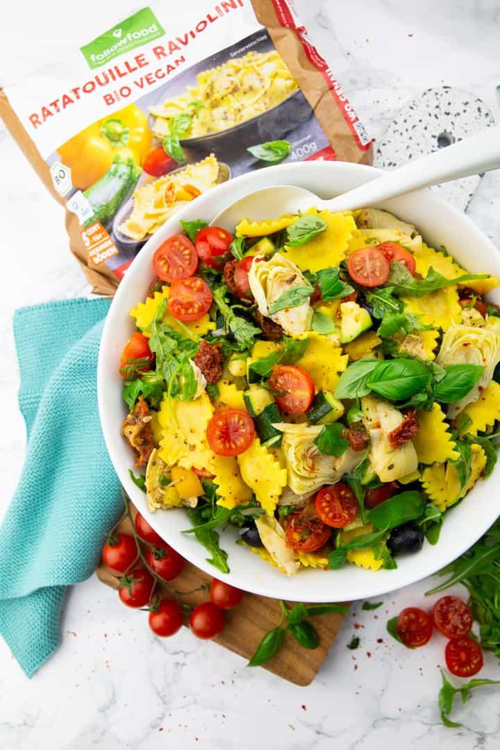 Ravioli Salat in einer weißen Schüssel auf einer Marmorplatte mit einer Packung Ratatouille Ravioli im Hintergrund