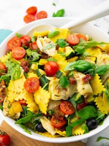 Ravioli Salat in einer weißen Schüssel mit einem weißen Löffel auf einer Marmorplatte mit Basilikum und Cherry Tomaten im Hintergrund