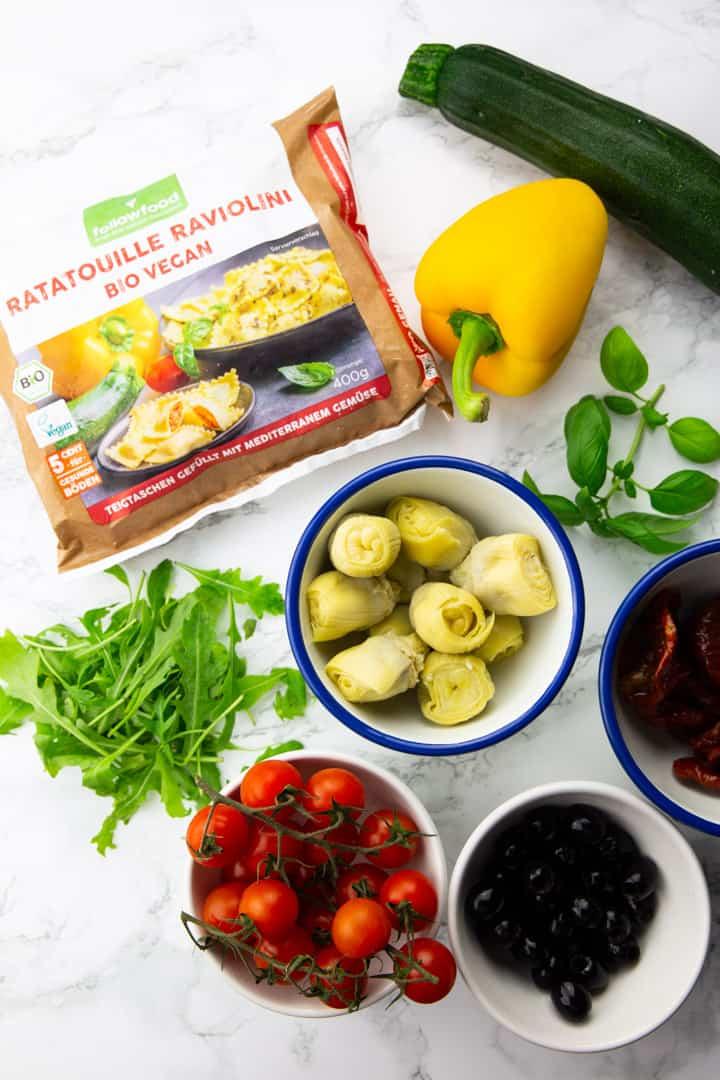 vier kleine Schüssen mit Cherry Tomaten, Oliven, getrockneten Tomaten, Artischockenherzen sowie Rucola, Basilikum, eine gelbe Paprika, eine Zucchini und eine Packung Ravioli auf einer Marmorarbeitsplatte