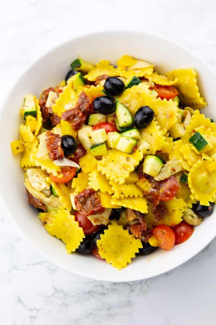 Ravioli mit Oliven, Artischocken, Zucchini, Paprika und Tomaten in einer weißen Schüssel auf einer Marmorplatte