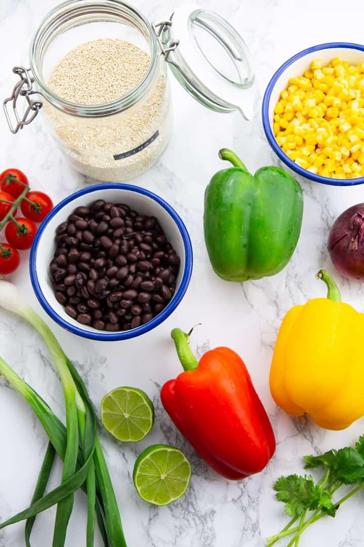 Zutaten für dieses Rezept (Paprika, Mais, schwarze Bohnen und Quinoa) auf einer Marmorplatte