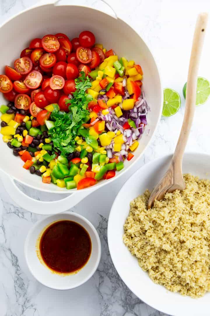 Drei Schüsseln mit einmal Quinoa, einmal Gemüse und Dressing auf einer Marmorplatte