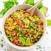 Quinoa Salat in einer weißen Schüssel mit einem Holzlöffel mit Limetten im Hintergrund