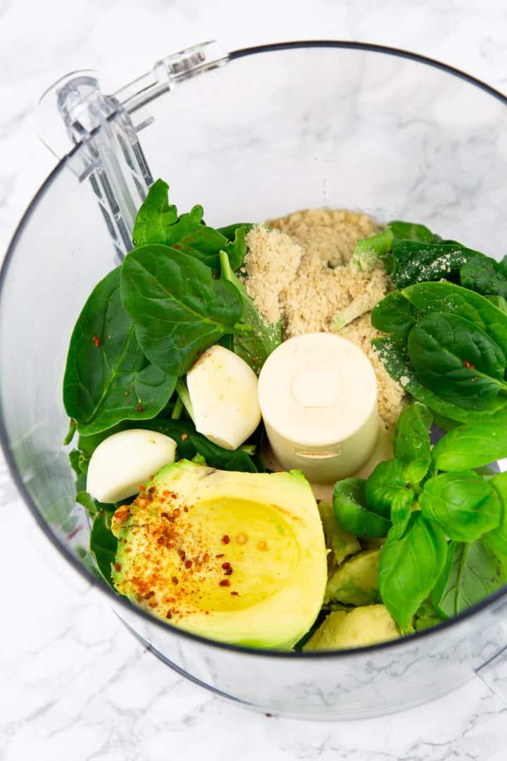 Avocado, Blattspinat, Knoblauch und Basilikum in einem Mixbecher