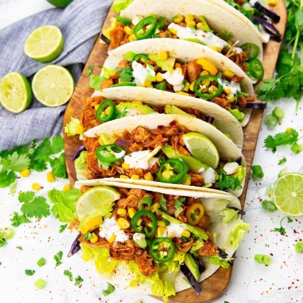 sechs Jackfruit Tacos auf einem Holzbrett mit Limetten im Hintergrund