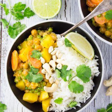 Kichererbsen Curry mit Reis in einem schwarzen Teller mit einer Gabel
