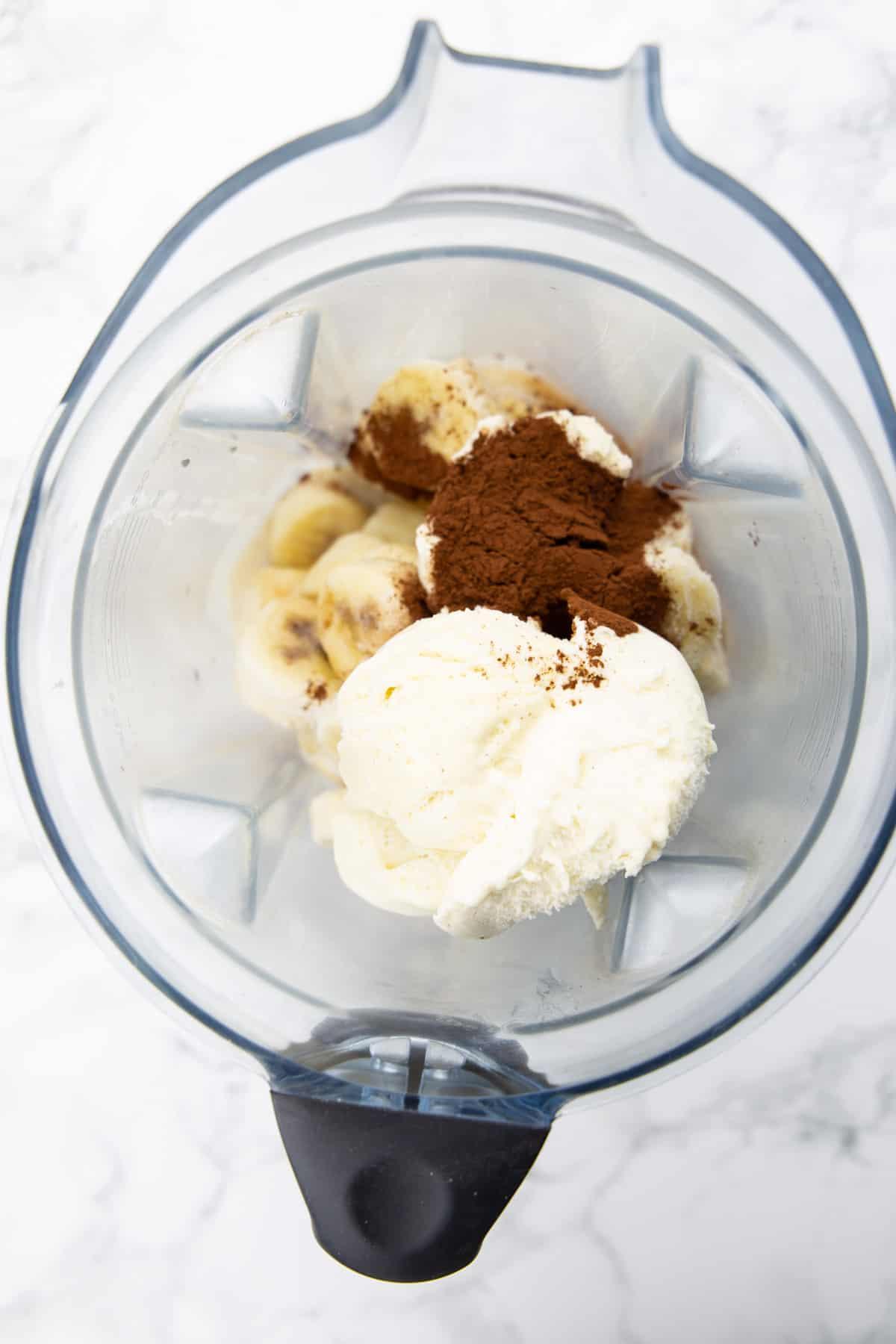 Gefrorene Bananen, Vanilleeis und Kakaopulver in einem Mixer auf einer Marmorplatte