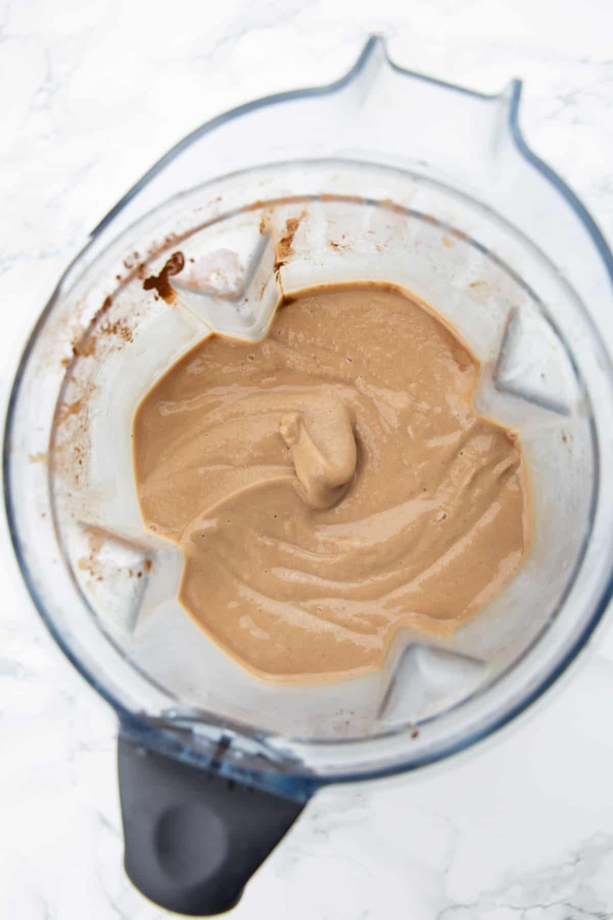 ein veganer Milchshake in einem Mixbehälter auf einer Marmorplatte