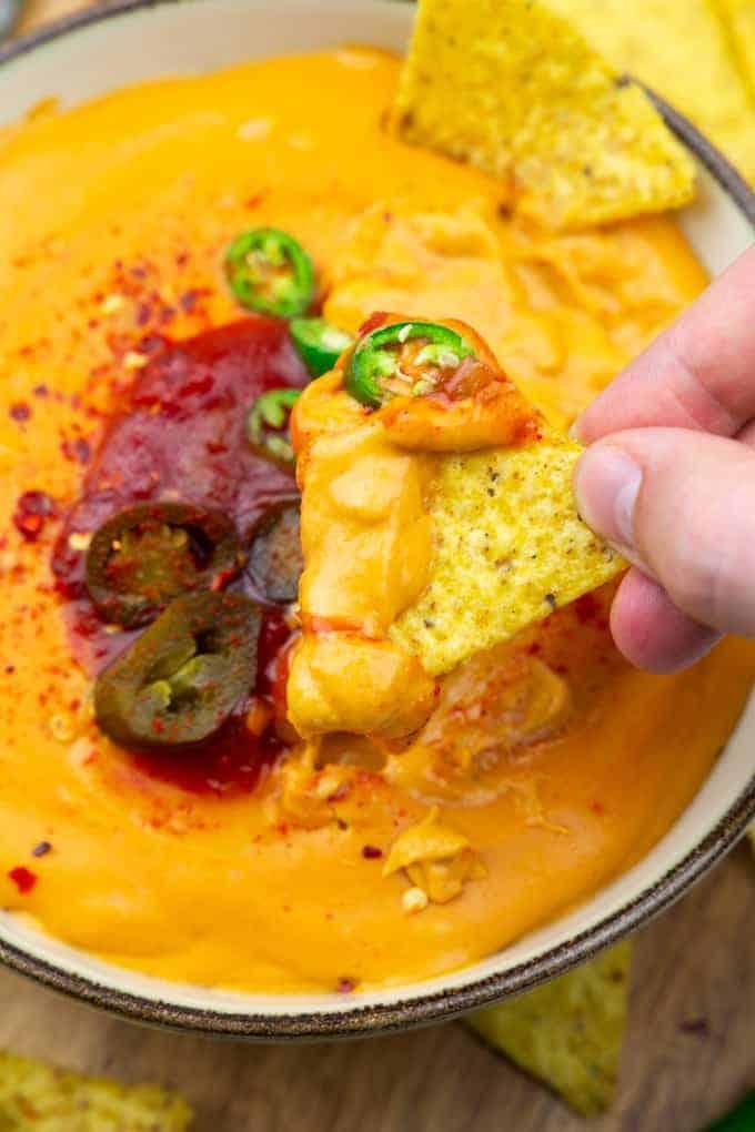 eine Hand tunkt Nachos in eine Schüssel mit Käsesauce