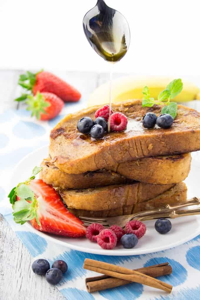 Ahornsirup läuft von einem Löffel auf einen Stapel French Toast