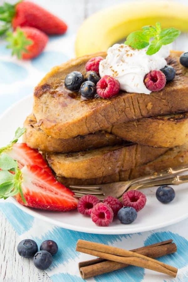 ein Stapel French Toast mit Beeren und Sahne auf einem weißen Teller
