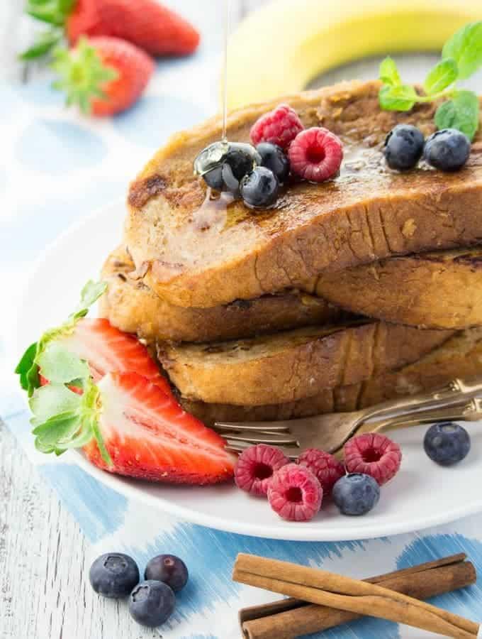 vier Scheiben French Toast auf einem Teller mit Beeren