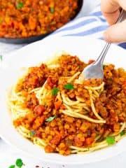 eine Hand rollt Spaghetti mit Linsenbolognese mit einer Gabel auf