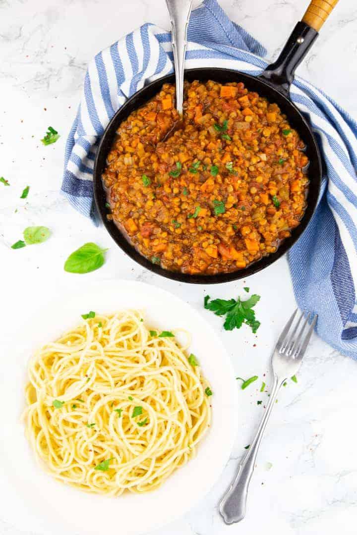 ein Teller mit Spaghetti mit einer Pfanne mit Bolognese Sauce im Hintergrund
