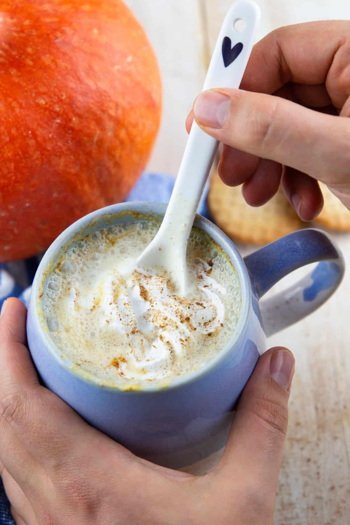eine Hand hält eine Tasse mit Pumpkin Spice Latte und rührt mit einem Löffel um