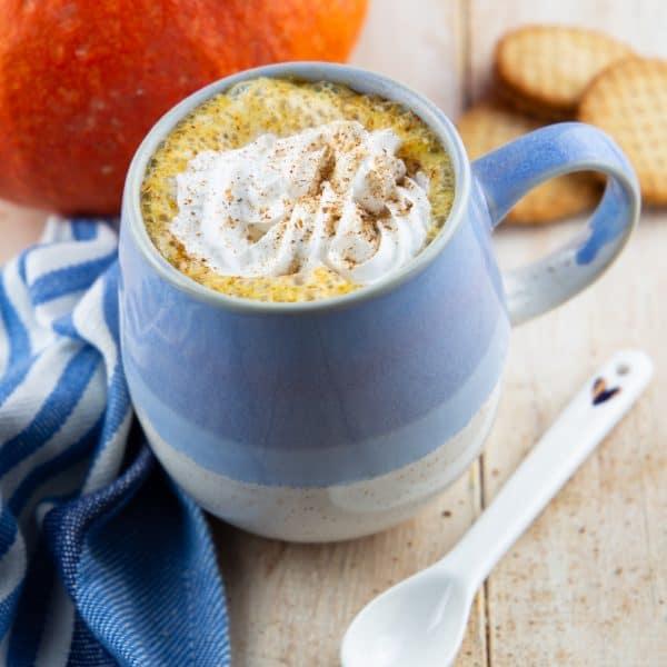 Pumpkin Spice Latte in einer blauen Tasse mit einem Kürbis im Hintergrund