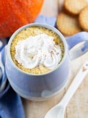 Pumpkin Spice Latte in einer blauen Tasse mit einem Kürbis und Keksen im Hintergrund
