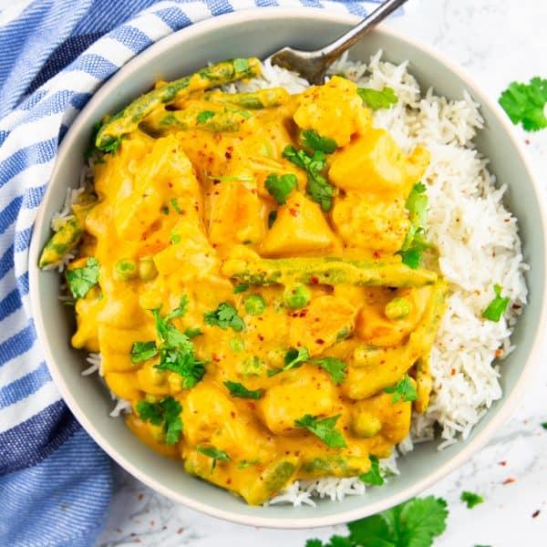 Korma mit Reis in einem grauen Teller mit einer Gabel