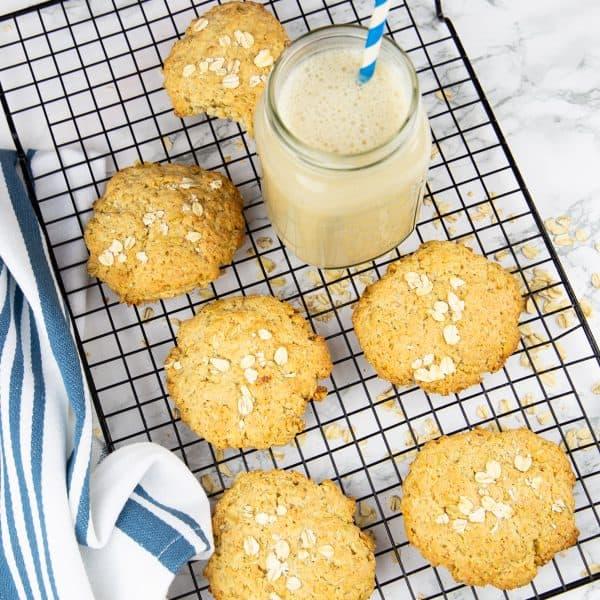 sechs Hafer Cookies auf einem Abkühlgitter mit einem Glas Mandelmilch