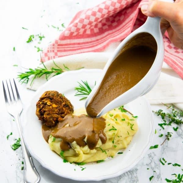 eine Hand gießt vegane Bratensoße aus einer Soßenschüssel über einen Teller mit Kartoffelpüree